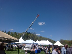 A firefighter stands high atop Family Fest, overlooking the festivities from the truck's ladder.
