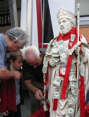 Pinning dollars on the statue at the St. Bart's Festival