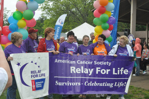 Cancer survivors hold the banner before taking the first lap.