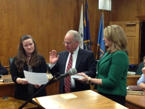 Returning committee member Ted Bourke, center, takes the oath of office, administered by Township Clerk Christine Gatti, left, while his wife, Kathleen, holds the Bible.