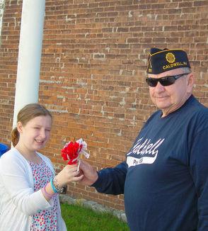 Carousel_image_da55fbb55e2e787cfbb1_lisa_brown_of_west_caldwell_this_year_poppy_girl_hands_james_caldwell_post__185_american_legion_commander_daniel_handy