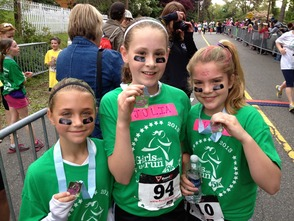 Girls on the Run participants show off their medals after completing the 5K