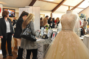 A bride-to-be stops to Sew 'N Sew Bridal and Tuxedo's table for information.
