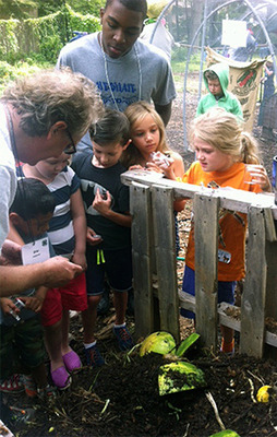 Gray Russell demonstrates composting to farm camp kids