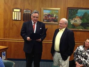Resident Steve Suskauer, right, receives a community service award through a proclamation read by Township Committee member Thomas McDermott.