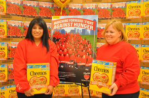 Denise Lewis and Jennifer Wilson of the Byram Store each hold a Cheerios Box, in which they are featured in a photo on back.