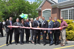 Joe Toscano, partner, readies to cut the ribbon, while flanked by fellow partners and dignitaries.