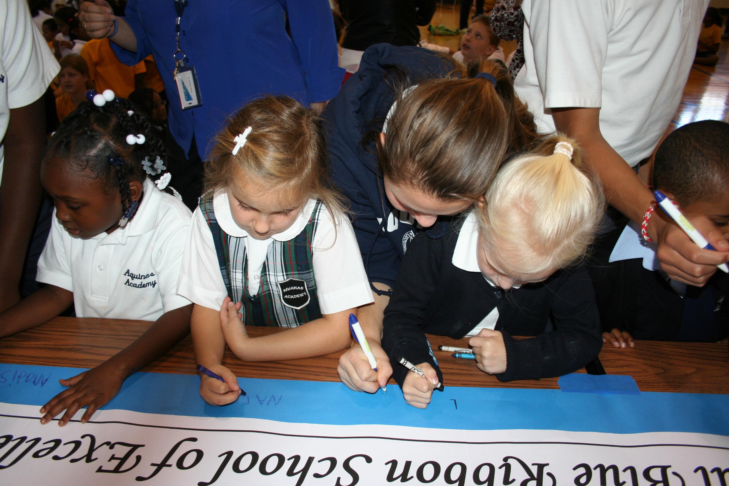 bf5b59edabf036cc0d56_Signing_the_Blue_Ribbon_Banner.jpg