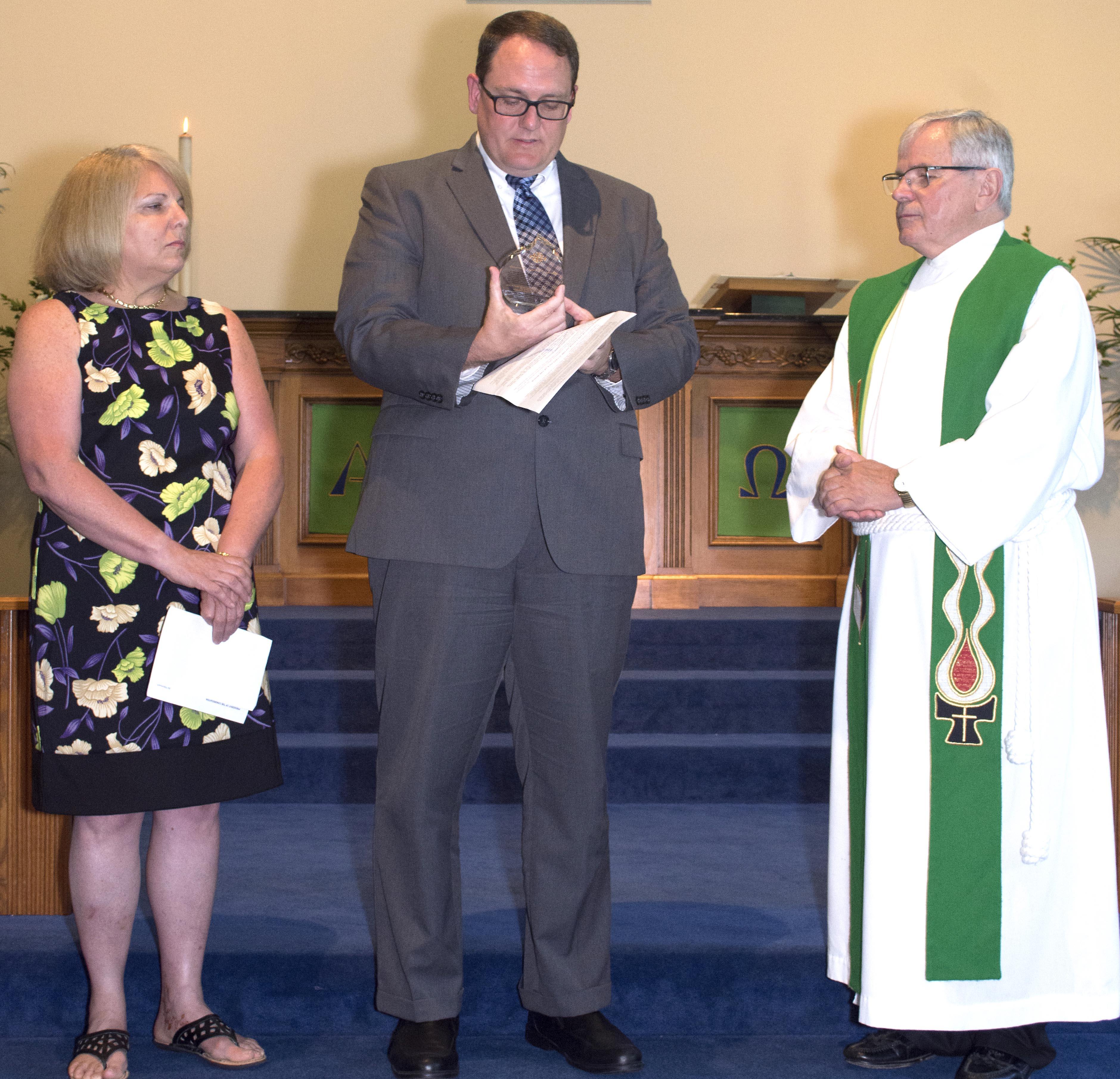 370c1c2975080bbc1acf_38944fe773c860b4206c_Bill_Ritterbusch_and_Kathy_Slater_Present_Pastor_Emeritus_Award_to_Reverend_Kennedy.jpg