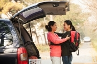 a3329b643b2b72318a15_stock-photo-28700406-mother-and-daughter-embracing-behind-car-on-college-campus.jpg