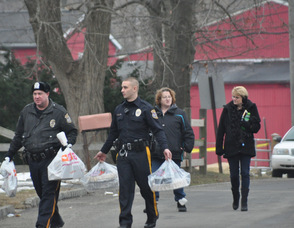 Police and loved ones of Clyde Schimanski, carry in food brought to the scene for those waiting.