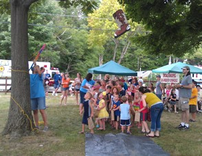 Children stand in line to knock down a cowboy boot shaped piñata.