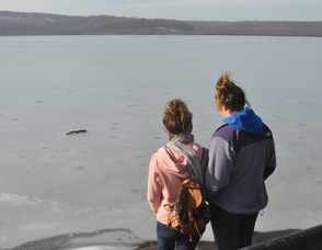 Two young girls stand by the lake.