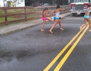 Young girls run barefoot in the street under a sprinkler.