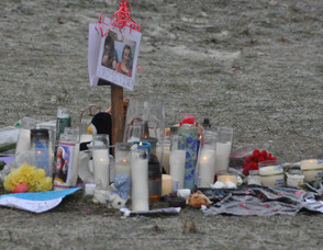 "Candles still burn early today in memory today of the two boys, as well as a photo of Schimanski, and his girlfriend Shelby LaBar, with a message, ""Stay Positive."""