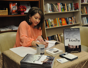 Author Lauren D. Fraser signs a book.