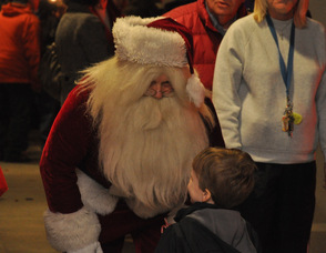 A little boy speaks to Santa.