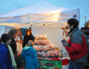 Customers choose decadent treats from the Candy Apple Shoppe; the merchant sold out of their chocolate-covered pretzels.