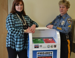 "Town Council Member and Sparta Municipal Alliance Chairperson, Molly Whilesmith and Sparta Police Corporal Susan Parkes stand next to the new ""Project Medicine Drop Box"" that is now located in the lobby of the Sparta Police Department. Prescription painkiller overdoses now kills more people in the U.S. than heroin or cocaine combined. Citizens can now legally dispose of unused medications at these drop boxes, 24-hours per day, seven days per week, 365 days per year."