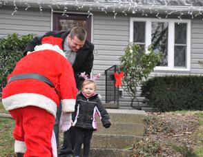 Sierra Arfken, age 2, greets Santa with a smile.