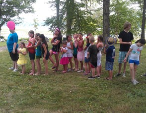 Children stand in line to engage in a game of bean bag toss.