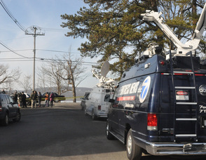 News vans wait near the lake.