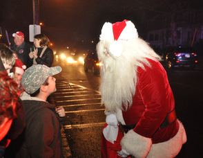 Santa hands out candy canes to children in front of the municipal building.