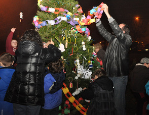 Residents of all ages decorate the town tree.