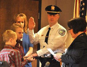 Andover Township Police Officer Eric Danielson is sworn in as lieutenant, by clerk/administrator Vita Thompson. He is surrounded by his family, wife Debbie, and children, Patrick and Matthew.