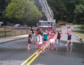 Children plays in the streets under a fire truck sprinkler.
