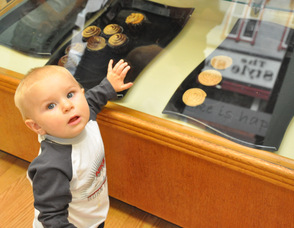 Asher Hollenback, age 10 months, eyes up baked goods in the case.