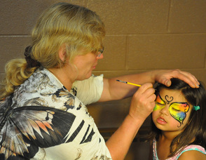 Parent Judy Kiederling paints a butterfly onto the face of Emelia Matti, age 4.