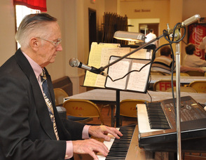 Dr. Richard W. Scott plays the keyboards at the luncheon.