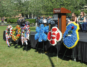 Wreaths lined up along the stage, representing all the agencies, and groups honored.