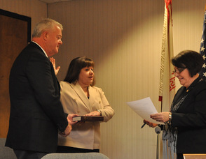 Committee member Janis McGovern sworn in by Administrator/Clerk Vita Thompson, as husband William McGovern holds the Bible.