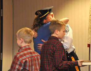 Eric Danielson embraces wife Debbie, after taking his oath, as sons Patrick and Matthew look on.