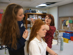 Becky Lawrence of Salon FiG teaches Courtney Milton (left) and Jennifer Dupre (sitting, center), how to create 'Hairspray' era styles.