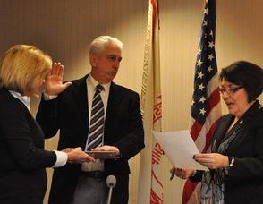 Tom Walsh sworn in as mayor by administrator/clerk Vita Thompson, as wife Debbie holds the Bible.