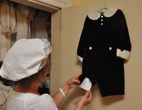 Allyn Perry inspects one of the outfits worn by the Cooper children in the early 20th Century.