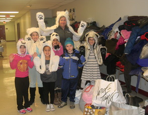 Principal Kelly Salazar with students dressed as polar bears in front of the coats