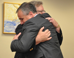 Wayne Dietz hugs Commissioner of the State Department of Labor and Workforce Development, Harold Wirths.