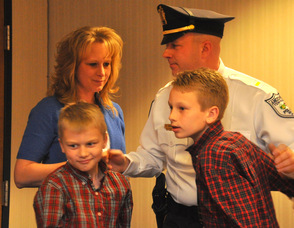Lieutenant Eric Danielson hugs wife Debbie, and sons Patrick, and Matthew.