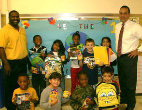 Jason Robinson of 8 to 8, left, stands with Ed Acevedo, Principal of Hazel Elementary, and students as they receive their school supplies