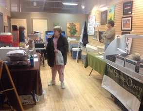A customer checks out items from Apple Ridge Farm, Maria's Gourmet Edibles, Pittenger Farms, and Coffee Coops.