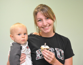 Marisa Hollenback with son Asher, 10 months, hold up a Cookies and Cream cupcake.