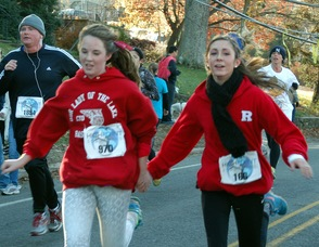 Two participants holding hands as they run.