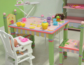 A tea party with one of the baby dolls in the girls' room at Chuckle Time.