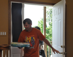 "Richard Hughes carries in food brought to the ""birthday party"" for the unsuspecting Max and Toni Zimmer."