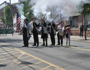 Revolutionary War Soldiers fire rifles into the air.