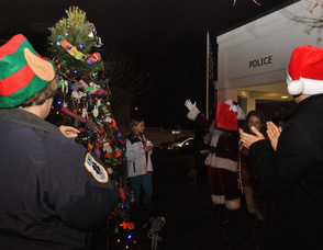 Santa holds up his hands in excitement as the tree is illuminated.
